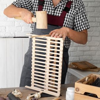 Homem trabalhando em objeto de madeira