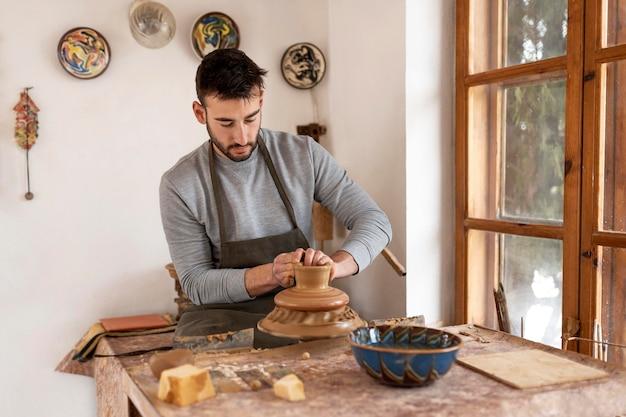 Homem trabalhando em oficina de cerâmica