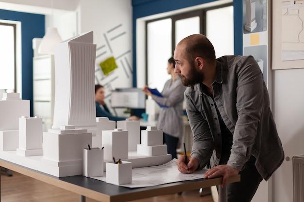 Homem trabalhando em projeto arquitetônico no escritório