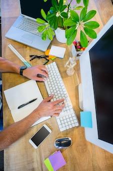 Homem, trabalhando, em, seu, escrivaninha, e, digitando, ligado, teclado, em, escritório