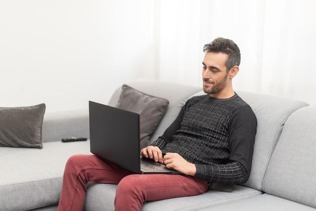 Homem trabalhando em seu laptop em casa, conceito de trabalho inteligente