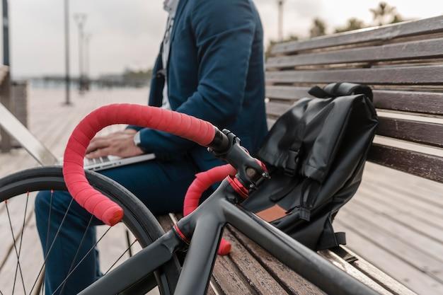 Homem trabalhando em um laptop ao lado de sua bicicleta ao ar livre