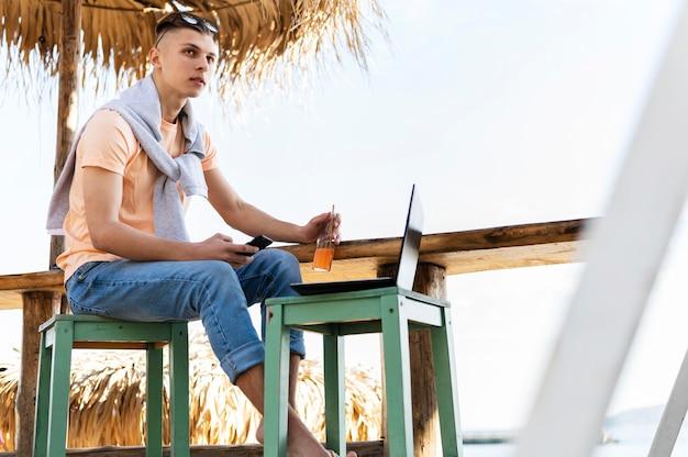 Homem trabalhando em um laptop do lado de fora
