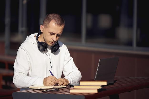 Homem trabalhando em um laptop e escrevendo em um caderno sentado na rua à mesa. distanciamento social durante o coronavírus
