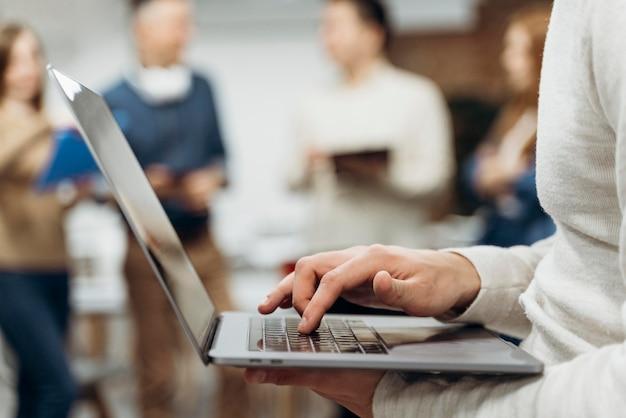 Homem trabalhando em um laptop em pé