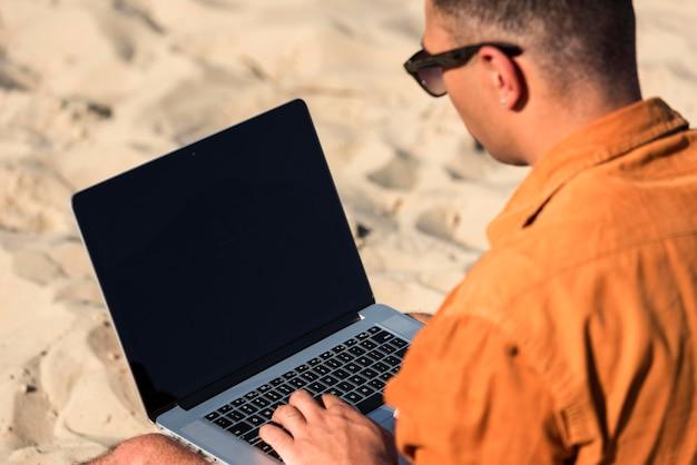 Homem trabalhando em um laptop na praia