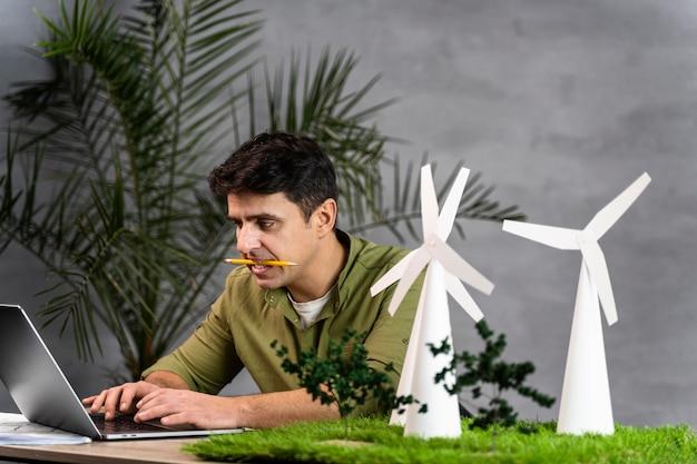 Homem trabalhando em um projeto de energia eólica ecologicamente correto com turbinas eólicas e laptop