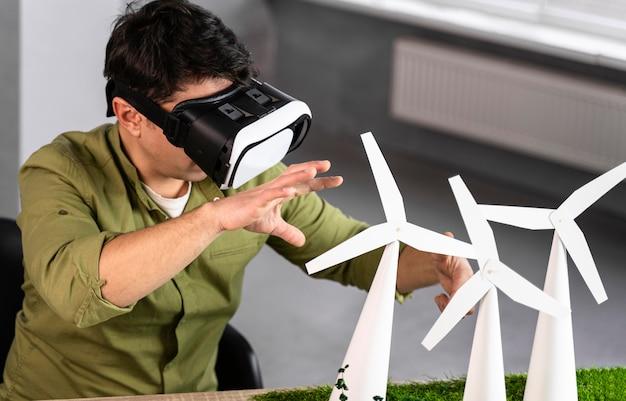 Homem trabalhando em um projeto de energia eólica ecologicamente correto usando um fone de ouvido de realidade virtual