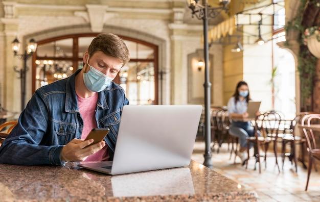 Homem trabalhando em um restaurante enquanto usava uma máscara facial com espaço de cópia