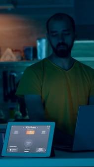 Homem trabalhando em uma casa inteligente, controlando o ambiente com um gadget wi-fi