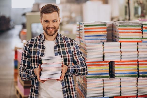 Homem trabalhando em uma gráfica com papel e tintas
