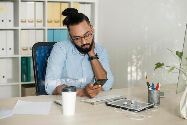 Homem trabalhando enquanto verifica o telefone