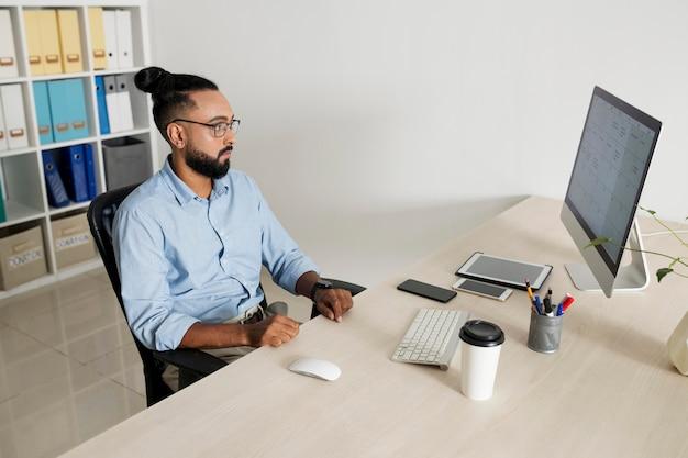 Homem trabalhando enquanto verifica seu dispositivo