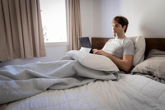 Homem trabalhando na cama, trabalhando em casa porque está doente, com um termômetro na boca.