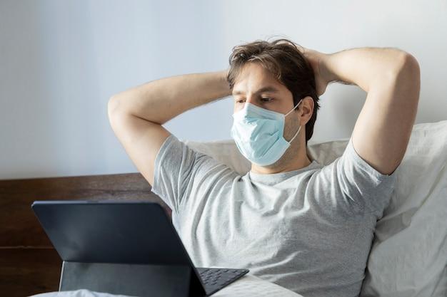 Homem trabalhando na cama, trabalhando em casa porque está doente. usando uma máscara sobre a boca e o nariz.