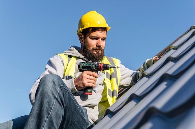 Homem trabalhando na vista frontal do telhado