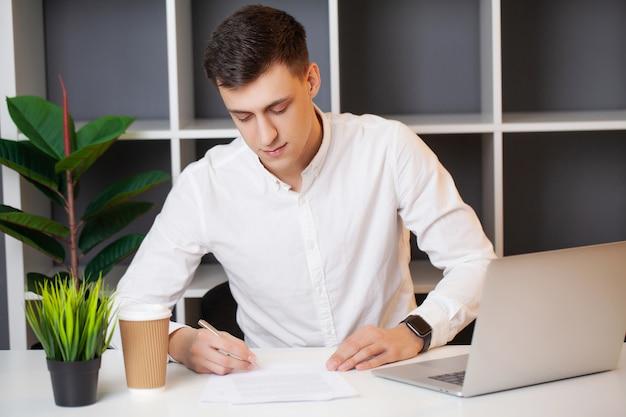Homem trabalhando no computador no escritório e preenchendo documentos