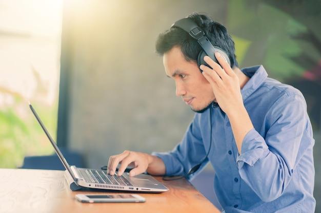 Homem trabalhando no computador ouvindo música no café, freelancer trabalha no café
