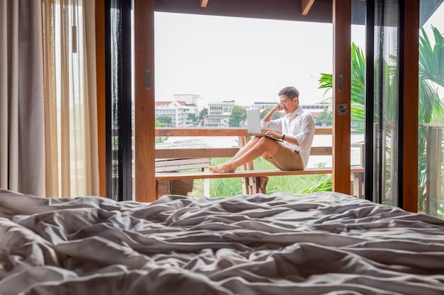 Homem trabalhando no computador portátil na varanda do hotel