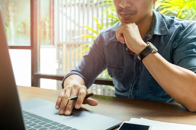 Homem trabalhando no laptop com celular na mesa de madeira