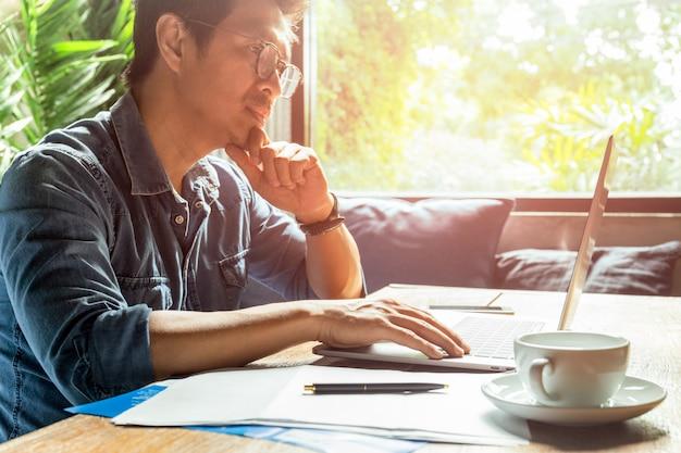 Homem trabalhando no laptop com papel de documento e xícara de café na mesa de madeira