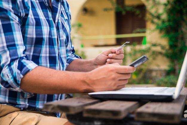 Homem trabalhando no laptop do jardim. contando dados financeiros banco, banco, conta.