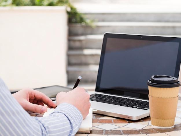 Homem trabalhando no laptop fora enquanto tomando café