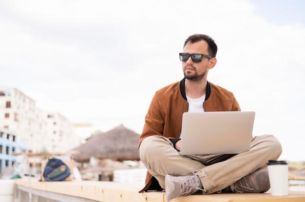 Homem trabalhando no laptop fora
