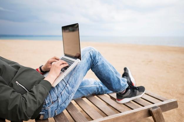 Homem trabalhando no laptop na cadeira de praia