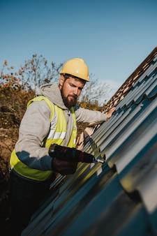 Homem trabalhando no telhado com uma furadeira
