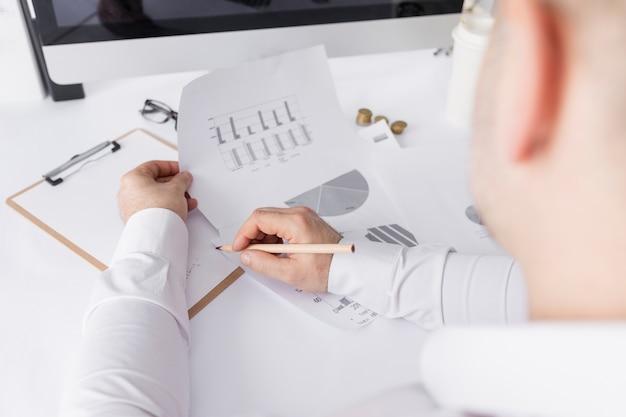 Homem trabalhando nos gráficos em seu balcão de negócios
