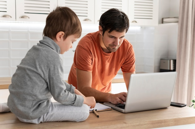 Homem trabalhando remotamente com criança, tiro médio