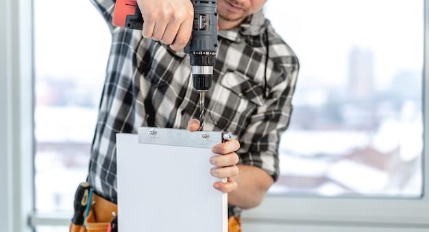 Homem trabalhando usando furadeira elétrica durante o processo de fabricação de móveis de madeira na oficina