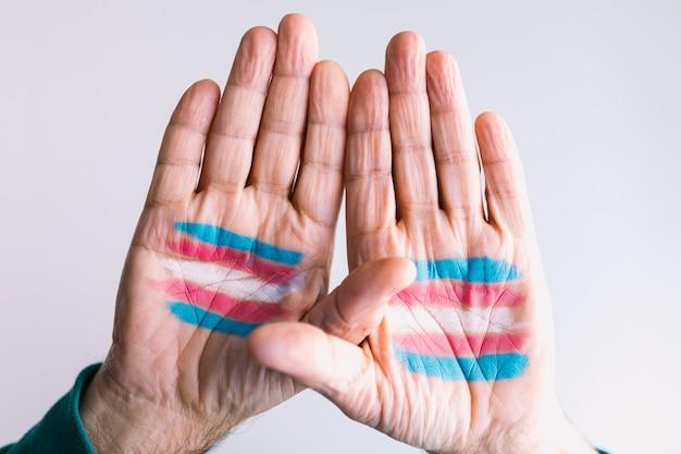 Homem transexual levanta as mãos com a bandeira transexual pintada nas palmas