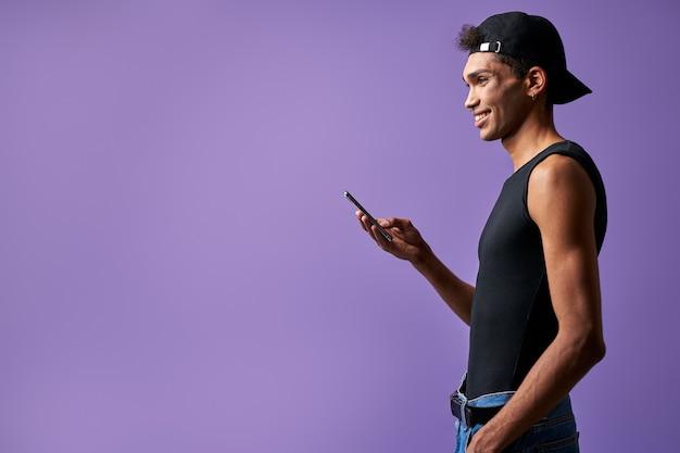 Homem transgênero sorridente com celular na mão, vista lateral em retrato de fundo roxo