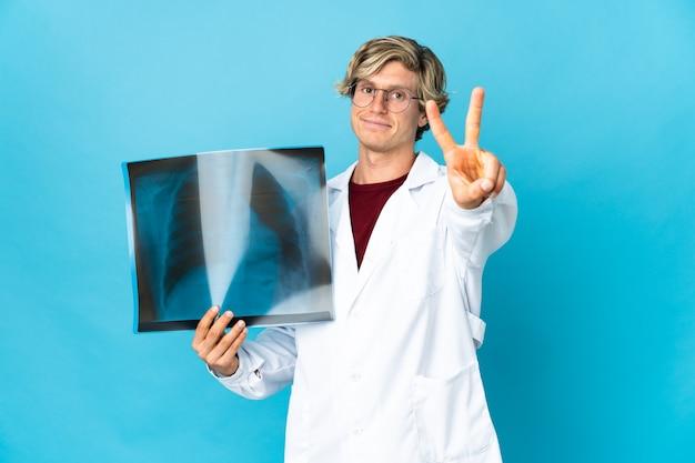 Homem traumatologista profissional sorrindo e mostrando sinal de vitória