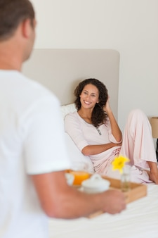 Homem trazendo café da manhã para sua esposa na cama
