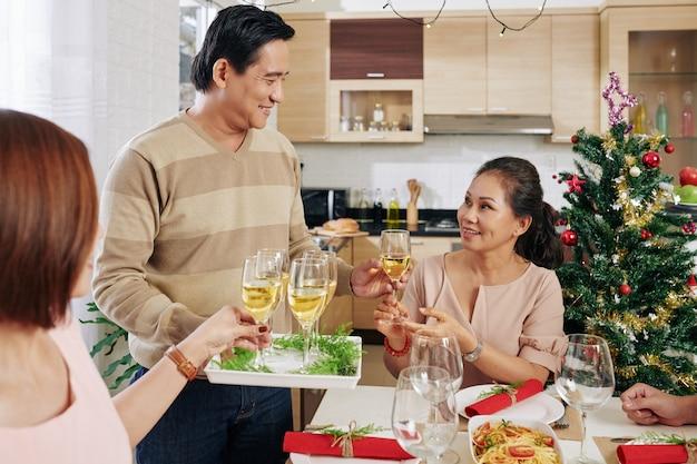 Homem trazendo champanhe para mesa de jantar