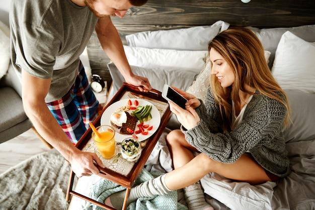 Homem trazendo mulher delicioso café da manhã