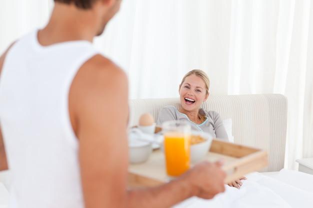 Homem trazendo o café da manhã para sua esposa