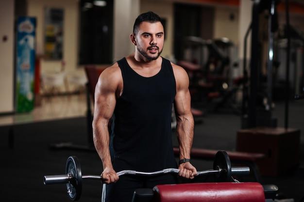 Homem treina bíceps no ginásio. indivíduo muscular do halterofilista que faz exercícios com um barbell.
