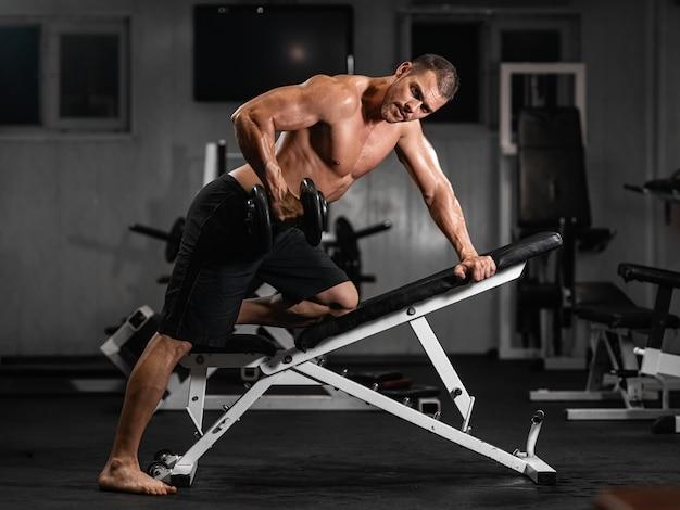 Homem treina no ginásio, atlético homem treina com halteres, bombeando seu bíceps