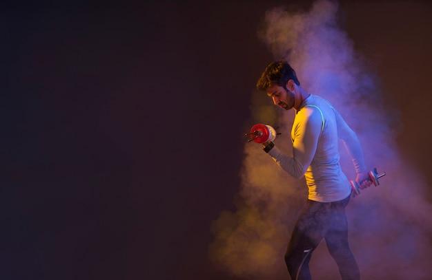 Homem, treinamento, com, dumbbells, em, colorido, vapor