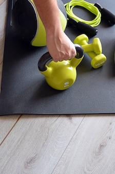 Homem treinando com kettlebell e medicine ball em casa