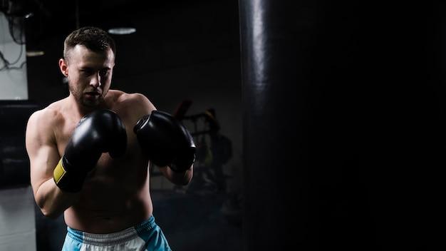 Homem treinando duro para uma competição de boxe com espaço de cópia