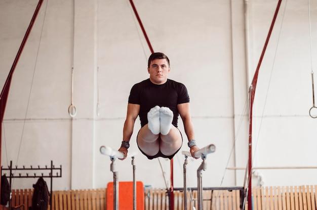 Homem treinando em barras paralelas