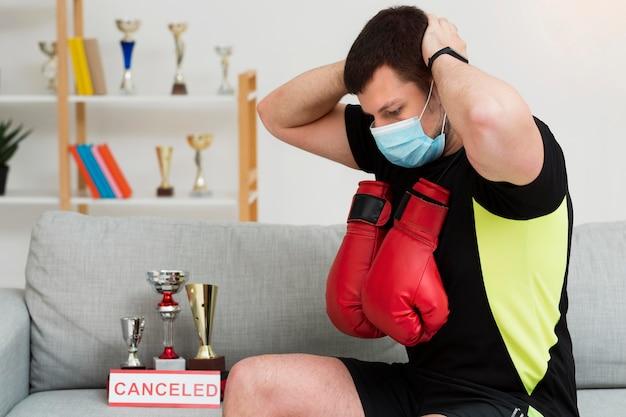 Homem treinando enquanto usava uma máscara médica dentro de casa