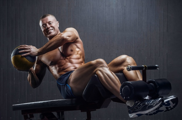 Homem treinando músculos abdominais na academia em fundo escuro