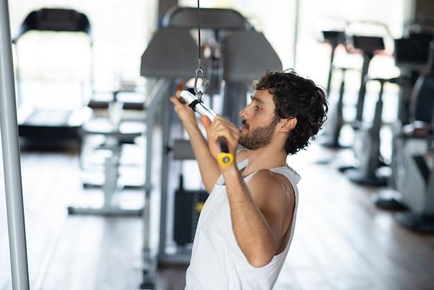 Homem treinando ombros e costas em uma academia