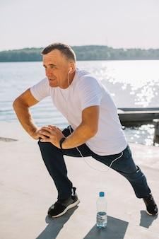 Homem treinando perto de um lago